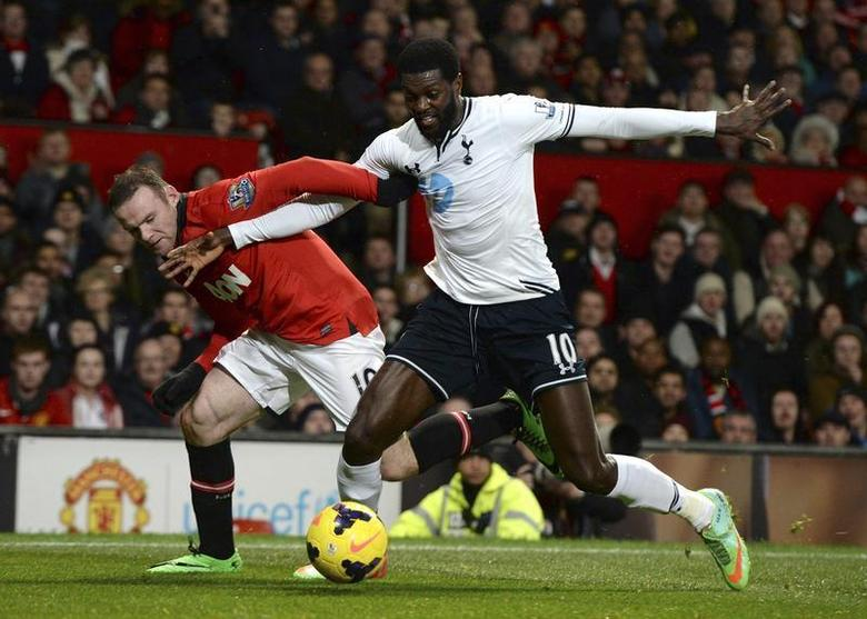 Manchester United's Wayne Rooney (L) is challenged by Tottenham Hotspur's Emmanuel Adebayor during their English Premier League soccer match at Old Trafford in Manchester, northern England January 1, 2014. REUTERS/Nigel Roddis