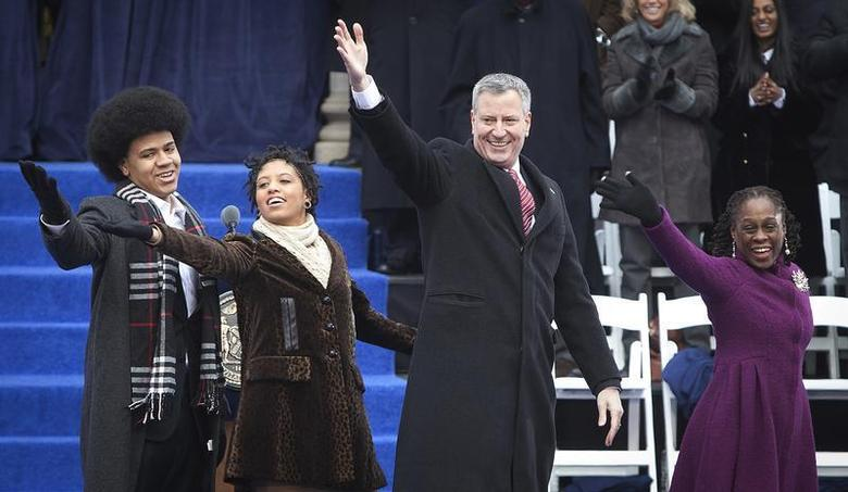 New mayor Bill de Blasio (2nd R) and his wife Chirlane de Blasio (R) blow a kiss to the crowd with their son Dante de Blasio (L) and daughter Chiara de Blasio after his public inauguration at City Hall in New York January 1, 2014. REUTERS/Carlo Allegri