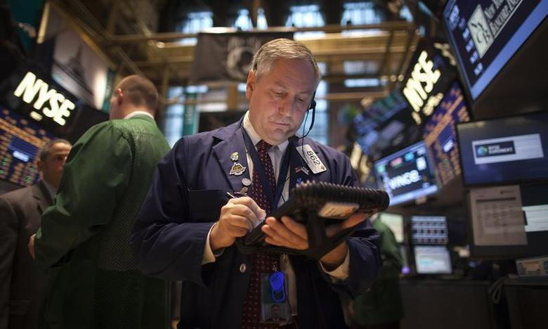 A trader works on the floor of the New York Stock Exchange during the opening bell in New York, November 27, 2013. REUTERS/Carlo Allegri