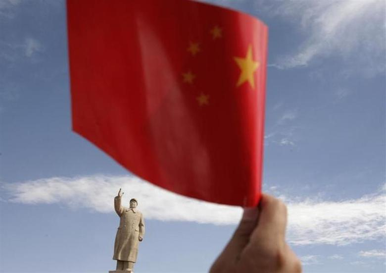 A spectator waves a Chinese flag in front of a statue of Chairman Mao Zedong during the Olympic torch relay in Kashgar, Xinjiang province June 18, 2008. REUTERS/Reinhard Krause/Files