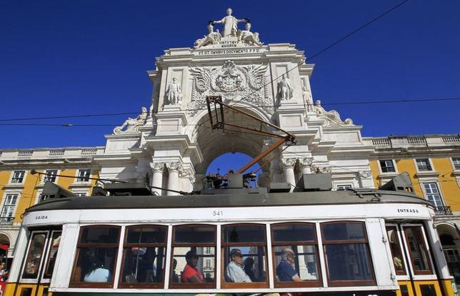 Passengers inside a tram pass in front of the main arch of Praca do Comercio square where the Finance Ministry is located, in Lisbon September 16, 2013. REUTERS/Jose Manuel Ribeiro