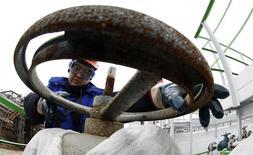 Los precios del petróleo cayeron el jueves, el primer día de operaciones del 2014, debido a que Libia, un productor de la OPEP, se preparaba para reanudar las operaciones en un importante yacimiento. En la foto de archivo, un trabajador petrolero en la refineria de Bashneft - Novoil en Ufa, Rusia. Abril 11, 2013. REUTERS/Sergei Karpukhin