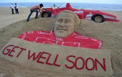 O artista indiano Sudarshan Pattnaik trabalha numa escultura de areia do heptacampeão mundial de Fórmula 1 Michael Schumacher para desejar boa recuperação ao piloto, em Puri, na Índia, nesta quinta-feira. 02/01/2014 REUTERS/Stringer