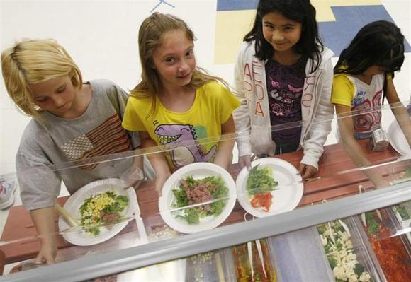 Students at Rose Hill Elementary School (L-R) Destiny Huges, Alexis Reubenstein and Sami Escadjeda choose the salad bar for lunch in Commerce City, Colorado May 1, 2012 instead of hamburgers and potatoes that were offered this day. REUTERS/Rick Wilking/Files