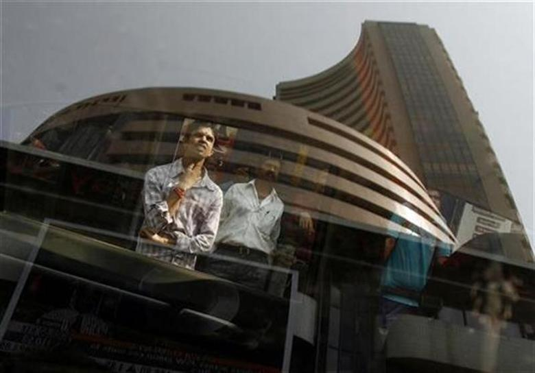 The Bombay Stock Exchange (BSE) building is reflected on a glass window as people look at a large screen displaying the Sensex on the facade of the building in Mumbai November 10, 2008. REUTERS/Arko Datta/Files