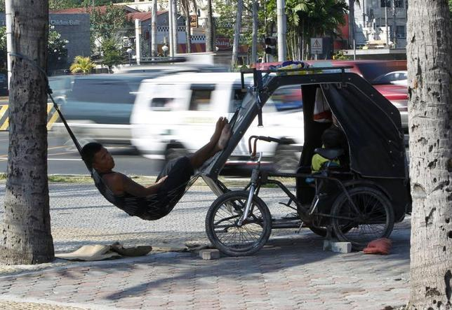 A bicycle cab driver takes a break on a hammock tied to a tree and his bicycle cab along a main street in Manila April 29, 2013. REUTERS/Romeo Ranoco