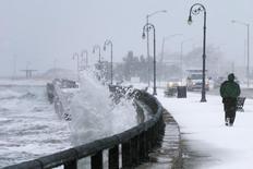 Homem corre enquanto ondas batem no quebra-mar durante nevasca de inverno, em Massachusetts, EUA, 2 de janeiro de 2014. Os governadores de Nova York e Nova Jersey declararam estado de emergência na quinta-feira, quando uma forte nevasca castigou o nordeste dos Estados Unidos, causando o cancelamento de milhares de voos e paralisando as viagens rodoviárias. REUTERS/Brian Snyder