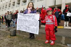 Kids celebrate with a placard the 45th birthday of seven-times former Formula One world champion Michael Schumacher in front of the CHU hospital emergency unit in Grenoble, French Alps, where Michael Schumacher is hospitalized January 3, 2014. REUTERS/Charles Platiau