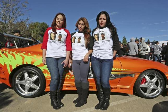 Alians Gudino (L), Arbiacely Gudino (C) and Monica Lovatos wear shirts commemorating ''Fast & Furious'' star Paul Walker and Roger Rodas during an unofficial memorial event in Santa Clarita, California December 8, 2013. REUTERS/Jonathan Alcorn/Files