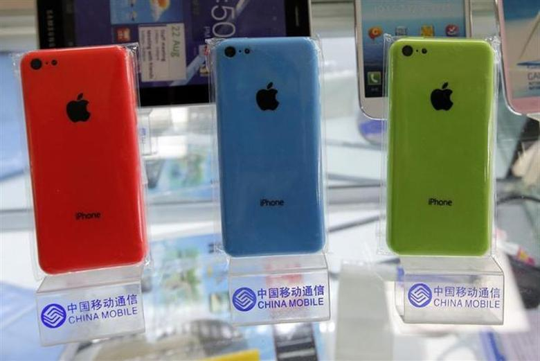 Apple's iPhone 5Cs phones are displayed on racks bearing the logo of China Mobile, at a mobile phone shop in Beijing December 23, 2013. REUTERS/Kim Kyung-Hoon/Files