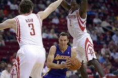 Los Angeles Lakers point guard Steve Nash (10) drives against Houston Rockets center Omer Asik (3) and point guard Patrick Beverley (2) during the second half at Toyota Center. Thomas Campbell-USA TODAY Sports