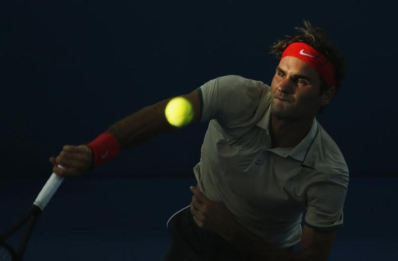 Roger Federer of Switzerland serves to Jeremy Chardy of France during their men's singles semi-final match at the Brisbane International tennis tournament in Brisbane, January 4, 2014. REUTERS/Jason Reed