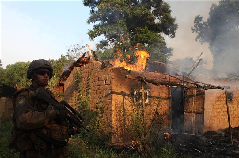 A French soldier patrols past a house on fire at a village in Bossangoa, north of the Central African Republic's capital Bangui January 3, 2014. REUTERS/Andreea Campeanu