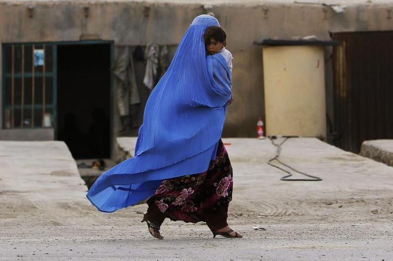 An Afghan woman wearing a burqa holds her child as she walks along a street on the outskirts of Kabul May 13, 2013. REUTERS/Omar Sobhani