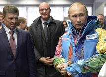 Russia's President Vladimir Putin (R), Organising Committee Head Dmitry Chernyshenko (C) and Deputy Prime Minister Dmitry Kozak (L) visit an Olympic volunteers centre in Sochi January 4, 2014. REUTERS/Alexei Nikolskiy/RIA Novosti/Kremlin