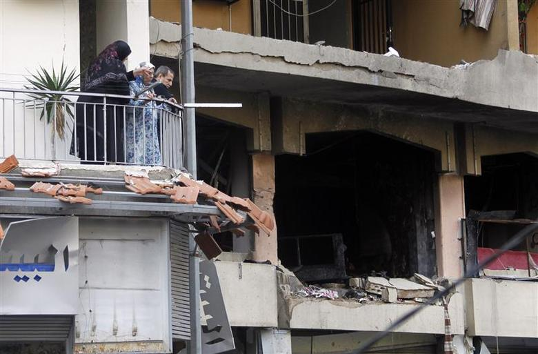 Residents stand on their balcony as they look at the site of an explosion that occurred yesterday in Beirut's southern suburbs, January 3, 2014. REUTERS/Sharif Karim