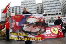Um fã francês da Ferrari segura bandeira com a imagem de Michael Schumacher em frente ao hospital em que o ex-piloto se encontra internado após um acidente de esqui, em Grenoble, na França. A condição de Michael Schumacher continua crítica, mas estável, disse neste sábado a agente do alemão quase uma semana depois que o heptacampeão de Fórmula 1 sofreu lesões cerebrais em um acidente de esqui no resort em Meribel, nos Alpes franceses. 3/01/2014. REUTERS/Charles Platiau
