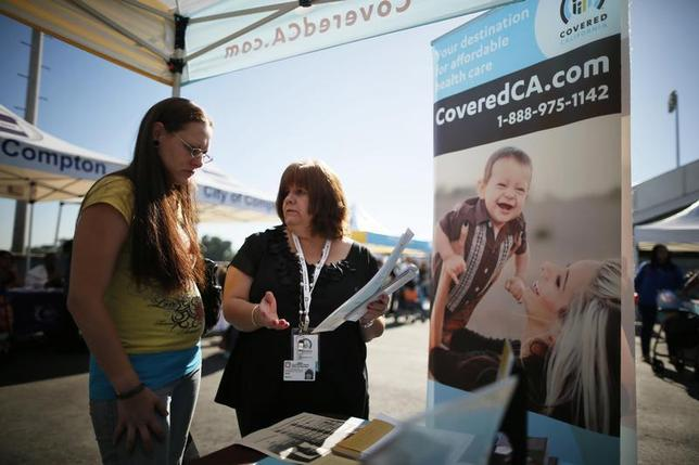 Maria Franco (R) explains health insurance to Violet Lucas-Barajas, 28, at an event to inform people about the Affordable Care Act and donate turkeys to 5,000 needy families, in Los Angeles, California, November 25, 2013. REUTERS/Lucy Nicholson