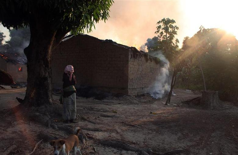 A woman looks at burning houses in Bossangoa, north of the Central African Republic's capital Bangui January 3, 2014. REUTERS/Andreea Campeanu