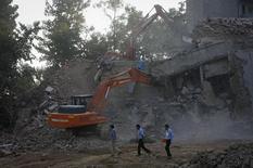 Máquina escavadeira remove destroços de um edifício em construção que desabou na localidade de Canacona, em Goa, na Índia. Pelo menos quinze trabalhadores foram mortos e muitos outros estão presos nos escombros do edifício, disseram neste domingo a polícia e a mídia. 5/05/2014. REUTERS/Danish Siddiqui