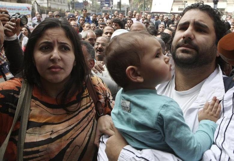 Alaa Abdel Fattah (R), one of the activists who was summoned by the public prosecutor on whether he had a role in the recent violent anti-Islamists protests, arrives with his wife and child to the public prosecutor's office in Cairo, March 26, 2013. REUTERS/Asmaa Waguih