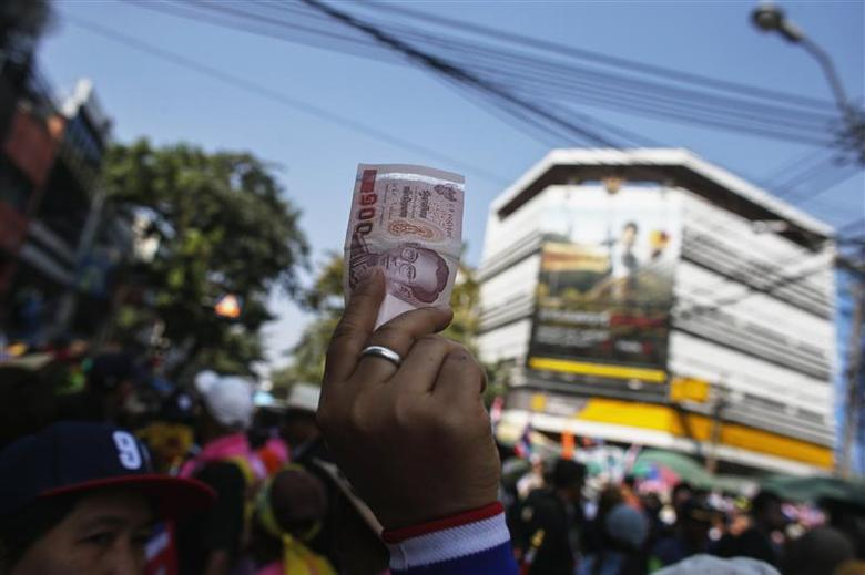 An anti-government protester holds up a Thai banknote to donate to anti-government protest leader Suthep Thaugsuban during a rally in central of Bangkok January 5, 2014. REUTERS/Athit Perawongmetha