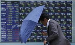 A man walks against strong wind and rain in front of a stock quotation board outside a brokerage in Tokyo October 2, 2013. REUTERS/Toru Hanai