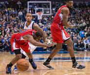 Jan 3, 2014; Dallas, TX, USA; Los Angeles Clippers point guard Chris Paul (3) falls to the court while dribbling past Dallas Mavericks shooting guard Monta Ellis (11) during the second half at the American Airlines Center. Paul sprained his right shoulder and did not return to the game. The Clippers defeated the Mavericks 119-112. Mandatory Credit: Jerome Miron-USA TODAY Sports