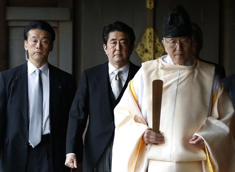 Japan's Prime Minister Shinzo Abe (C) is led by a Shinto priest as he visits Yasukuni shrine in Tokyo December 26, 2013. REUTERS/Toru Hanai