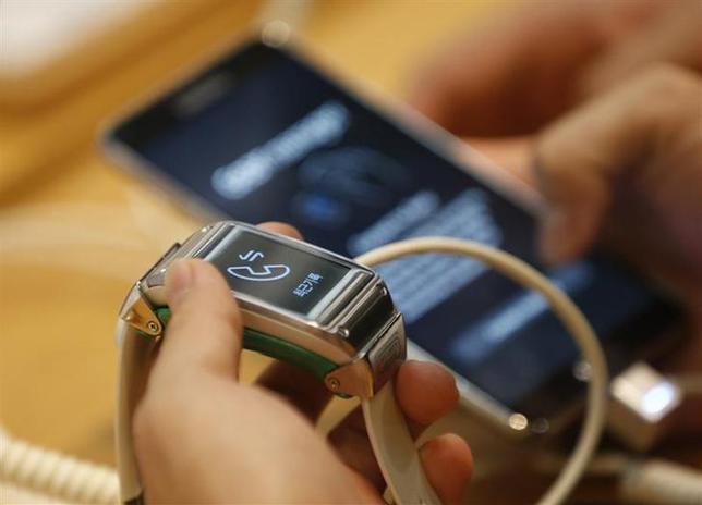 1月5日、米ラスベガスで今週開催される家電見本市「CES」では身につけて利用する「ウエアラブル端末」が展示され、注目を集めそうだ。写真は韓国サムスンの腕時計型端末「ギャラクシー・ギア」。ソウルで昨年10月撮影(2014年 ロイター/Kim Hong-Ji)
