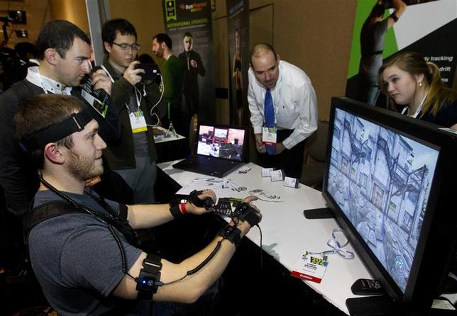 YEI Technology's Chris George plays a computer game with PrioVR, a virtual reality gaming accessory, during ''CES Unveiled,'' a media preview event to the annual Consumer Electronics Show (CES), in Las Vegas, Nevada, January 5, 2014. REUTERS/Steve Marcus