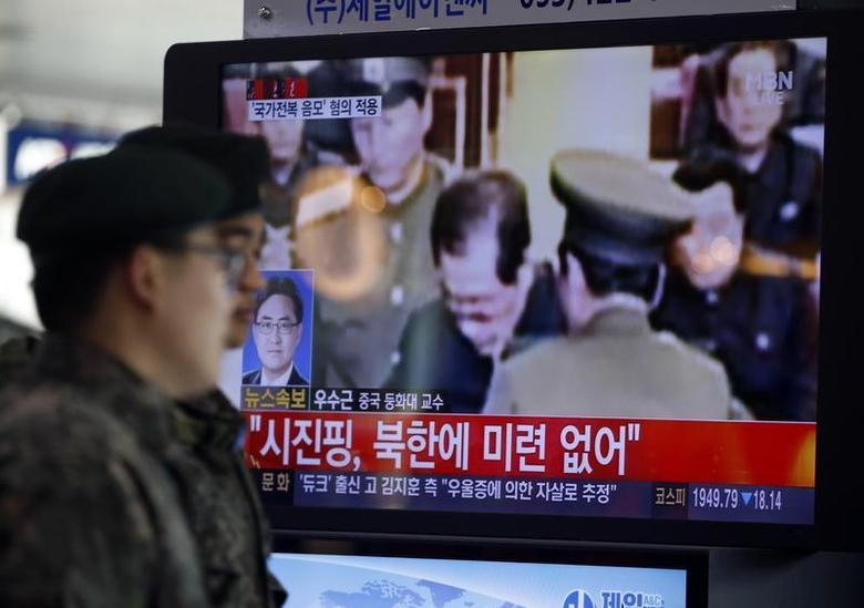 South Korean soldiers walk past a television showing reports on the execution of Jang Song Thaek, who is North Korean leader Kim Jong Un's uncle, at a railway station in Seoul December 13, 2013. REUTERS/Kim Hong-Ji