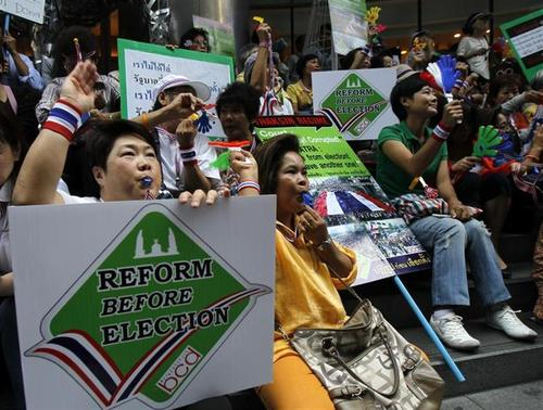Anti-government protesters blow whistles and hold placards during a rally at Silom road in central Bangkok January 6, 2014. REUTERS/Chaiwat Subprasom