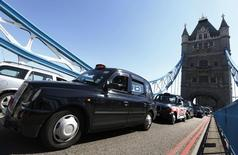 Taxi drivers in traditional black cabs drive slowly across Tower Bridge in protest at not being allowed to drive in the Olympic Lanes during the London 2012 Olympic Games July 23, 2012. REUTERS/Luke MacGregor