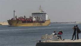 Unas personas observan el paso de un barco por el Canal de Suez en los alrededores del puerto de Ismailia, Egipto, jun 13 2013. Egipto ha invitado a 14 consorcios a que presenten sus planes para el desarrollo de obras en la zona del Canal de Suez, dijeron funcionarios el lunes, con el propósito de atraer más buques e ingresos destinados a fortalecer las finanzas del país. REUTERS/Stringer