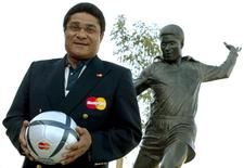 Portuguese soccer player Eusebio holds a soccer ball and poses in front of his statue at the entrance of the Luz Stadium in Lisbon in this July 3, 2004 file photo. REUTERS/Stringer/Files