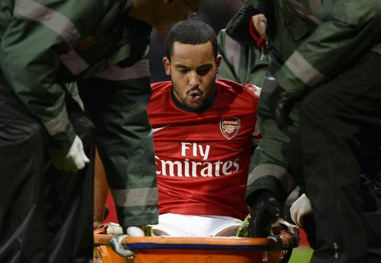 Arsenal's Theo Walcott is stretchered off the pitch during their English FA Cup soccer match against Tottenham Hotspur at the Emirates stadium in London, January 4, 2014. REUTERS/Dylan Martinez