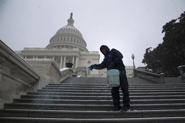 A worker spreads an anti-ice mix on the steps of the U.S. Capitol as light snow flurries fall in Washington December 8, 2013. REUTERS/Jonathan Ernst