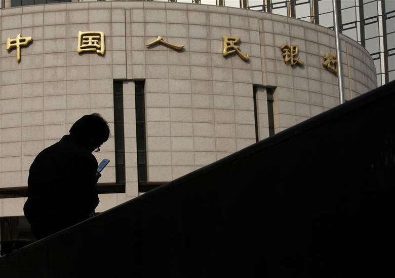 A man sits in front of the headquarters of the People's Bank of China, the central bank, in Beijing in this October 17, 2013 file photo. REUTERS/Kim Kyung-Hoon/Files