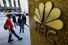 Pedestrians walk past an NBC logo outside Rockefeller Center in New York April 30, 2013. REUTERS/Lucas Jackson