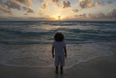 A man watches the sunrise on New Year's Day at Gaviota Azul beach in Cancun January 1, 2014. REUTERS/Victor Ruiz Garcia