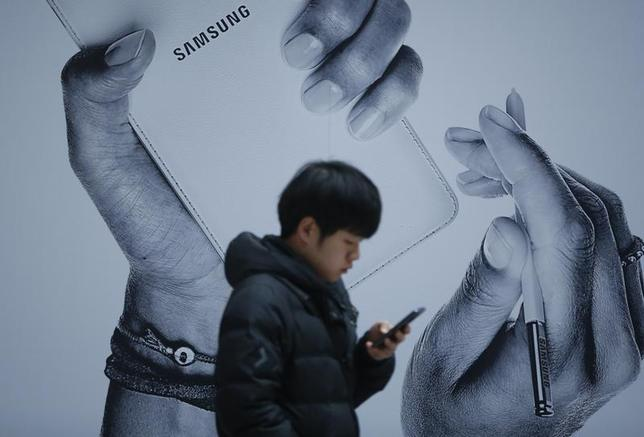 A passenger using his mobile phone walks past an advertisement promoting Samsung Electronics' Galaxy Note 3 at its exhibition hall at a railway station in Seoul November 25, 2013. REUTERS/Kim Hong-Ji /Files