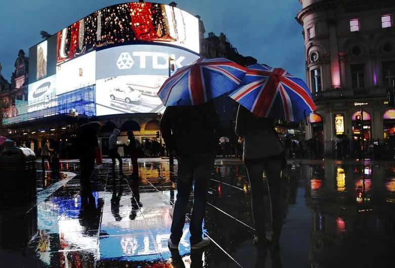 People stand under Union Flag umbrellas during rain in Piccadilly Circus in London November 8, 2013. REUTERS/Luke MacGregor