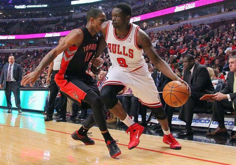 Dec 31, 2013; Chicago, IL, USA; Chicago Bulls small forward Luol Deng (9) is defended by Toronto Raptors shooting guard DeMar DeRozan (10) during the first quarter at the United Center. Mandatory Credit: Dennis Wierzbicki-USA TODAY Sports - RTX16YJX