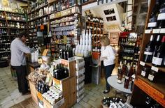 A customer keeps his purchases in a bag at a wine shop in Alella, near Barcelona October 30, 2013. REUTERS/Albert Gea
