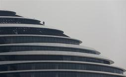 A labourer works on the roof of a new building in Beijing, January 6, 2014. REUTERS/Jason Lee