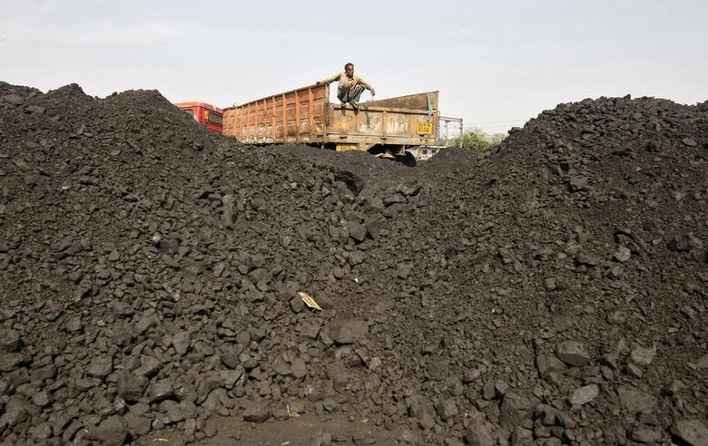 A worker sits on a truck as he waits for the loading of coal at a railway coal yard on the outskirts of Ahmedabad November 25, 2013. REUTERS/Amit Dave/Files