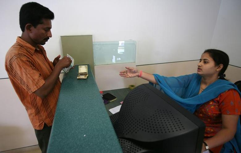 A customer deposits money at the teller counter of a bank's microfinance division in Mumbai October 25, 2008. REUTERS/Punit Paranjpe/Files