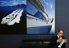 A man reads underneath pictures advertising yachts at the London Boat Show at the ExCeL centre in London January 6, 2014. REUTERS/Luke MacGregor