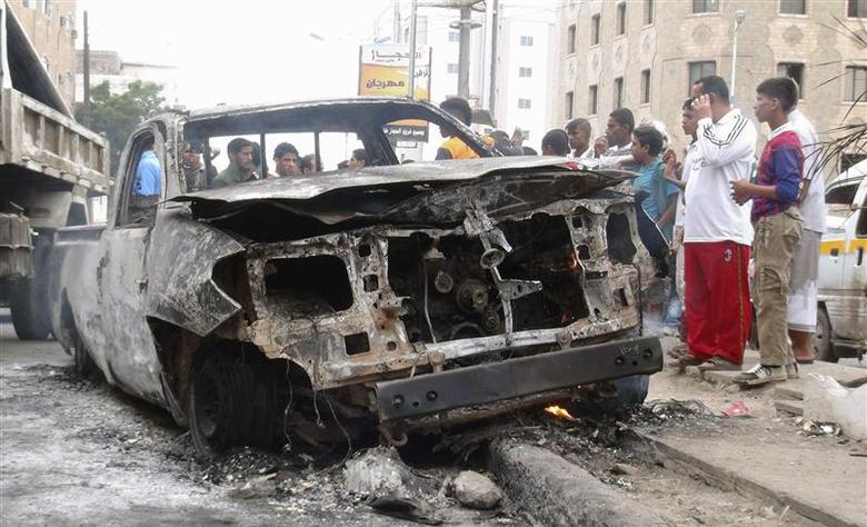 People gather around the vehicle of a Yemeni intelligence officer that was destroyed by a blast from an explosive device in the southern Yemeni port city of Aden January 7, 2014. REUTERS/Stringer